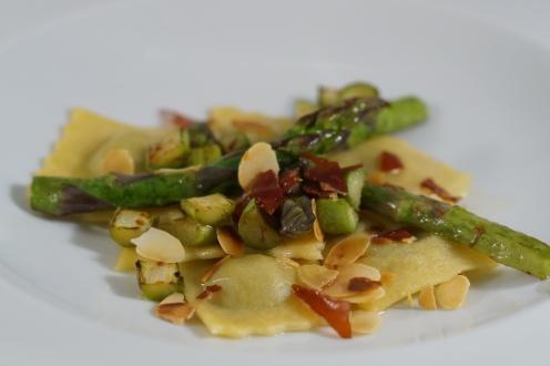 Spargel Ravioli, grüne Spargeln, geröstete Mandeln und Prosciuttosplitter